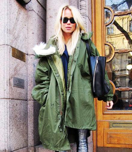 Blonde Frau mit grünem Parka.