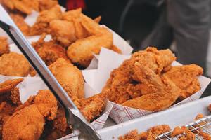 Ein Typ füttert seine Freundin mit Chicken McNuggets, im Nagelstudio.
