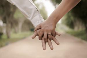 Paar hält Händchen und zeigt ihren Verlobungsring.
